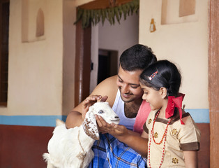 Father showing a goat to his daughter