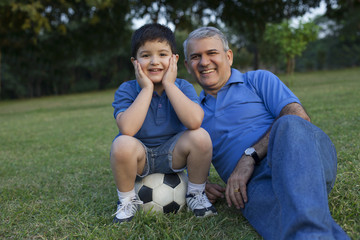 Portrait of grandfather and grandson in a park