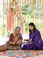 Mother and daughter making a rangoli