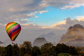 Colorful hot air balloon is flying over the mountain and jungle at sunrise