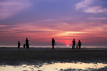 A group of people watching the sun setting over the horizon with beautiful twilight in the background
