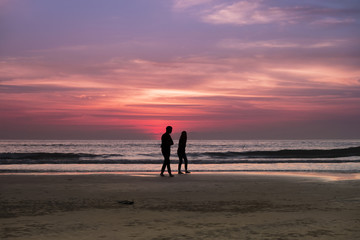 A couple walking by the beach when sundown with beautiful twilight in the background. Image contain motion blur and grains due to low light ambiance and movement.