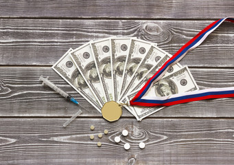 Medal with ribbon of Russian flag color, dollar bills, syringe, tablets against the background of a wooden table. Doping. Violation of rules, corruption.