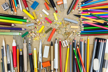 artist work tools on brown recycled paper top view. multicolored pencils, pastel chalk, sharpener, eraser.