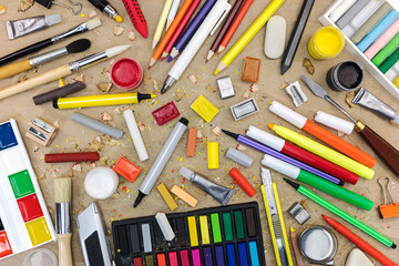 colorful school supplies on recycled paper background: watercolor, colored pencils and markers, chalks, various paintbrushes, sharpener