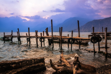 After sunset on Lake Atitlan viewed from the shores of Panajachel in Guatemala with an old rickety pier and some driftwood in the foreground.