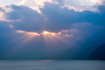 Sun-beams at sunset over Lake Atitlan viewed from the shores of the lake in the small village of Panajachel in Guatemala.