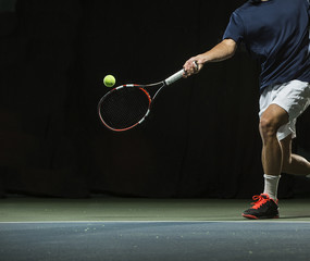 Close up photo of a man swinging a tennis racquet during a tennis match