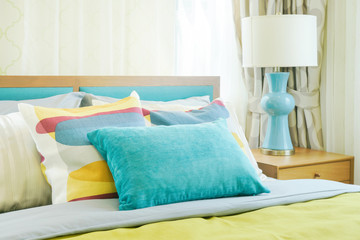 Closeup pillows on bed, yellow and green color scheme bedding