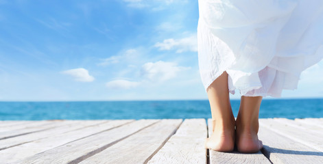 Beautiful feet of a woman in white dress on a wooden pier.  Sea and sky background. Vacation, resort and freedom concept.