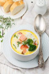 Salmon creamy soup with vegetables - potatoes, carrots, tomatoes and broccoli in a white bowl on bright wooden table