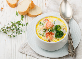 Chowder with salmon, potatoes, carrots, tomatoes and broccoli in a white bowl on bright wooden table