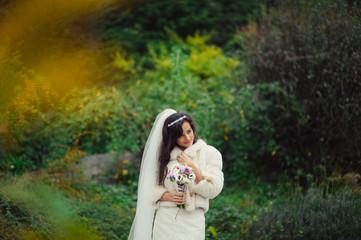Beautiful brunette bride on a walk in autumn park