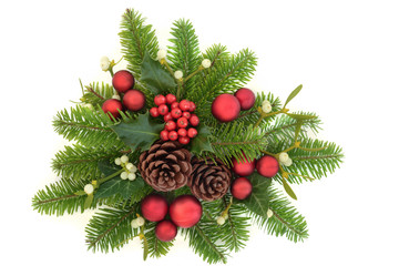 Decorative christmas greenery with holly ivy, mistletoe, fir, red bauble decorations and pine cones on white background.