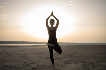 young fit woman training yoga poses in desert during the sunset or sunrise, female in black sportswear do stretching exercises
