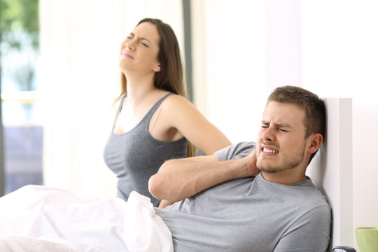 Couple suffering ache in a not comfortable bed
