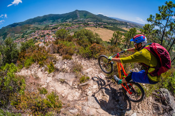 Mountain biker in sunny Tuscany - flying towards old town in the valley