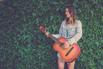 Female playing guitar against green leaf wall background