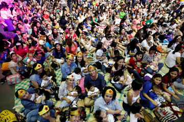 Filipino mothers hold their babies during a one-minute simultaneous breastfeeding event, as a way to promote breastfeeding, on the sidelines of this year's ASEAN foreign ministers summit, in Manila