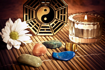 Ying yang, i-ching with healing stones, candle and a daisy flower like a concept of chinese oriental astrology