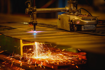 Worker cutting steel plate with acetylene welding cutting torch and bright sparks in factory