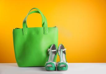 Stylish green handbag and high heels on orange background