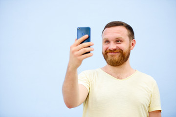 A man makes faces in a funny and humorous phone makes serious faces, an advertising company
