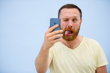 man makes faces in a funny and humorous phone shows a language, an advertising company