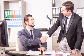 Business partners shaking hands in the office. Two businessman in formal suits shaking hands in corporate office eviroment