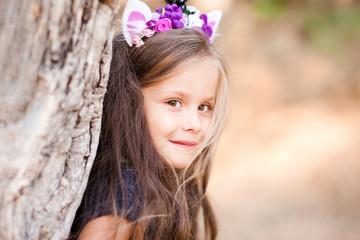 Smiling baby girl 4-5 year old posing outdoors. Looking at camera. Wearing handmade headband. Childhood.