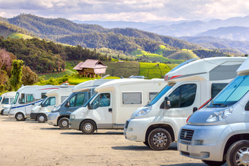 Close up motorhomes parked in a row on background green terraced rice field nature landscape.