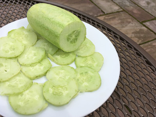 White variety of cucumber on a plate showing whole and sliced cucumber