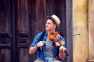 Young traveller men playing violin in ancient city in French style