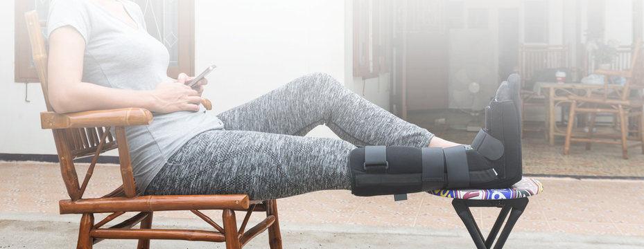 woman with black cast on leg sitting on wood chair, body injury concept