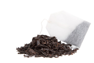 A bag of black tea and tea leaves on a white background