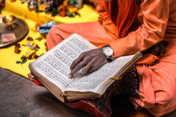 Old sadhu hand wearing hand watch pointing at line of holy book Varanasi, India.