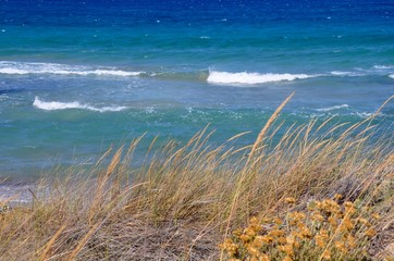 Typical view of cyclades islands nature, dry beige grass and turquoise blue sea