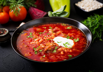 Traditional Ukrainian Russian borscht with white beans on the black bowl