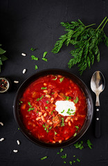 Traditional Ukrainian Russian borscht with white beans on the black bowl and ingredients for borsch. Flat lay. Top view.