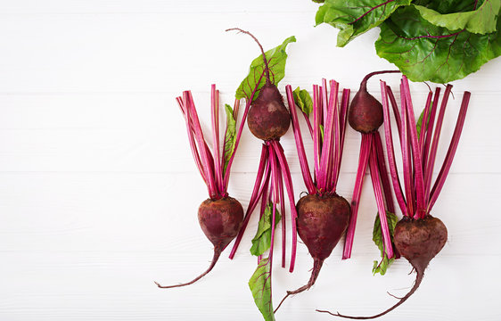 Young beetroot with a tops on a white background. Flat lay. Top view