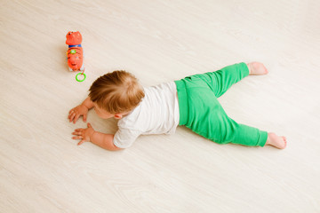 toddler boy white t-shirt and green pants lies on his stomach on the wooden floor. the view from the top