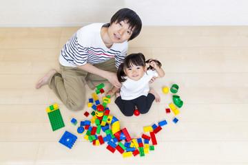 お父さんとブロック遊びをする幼い女の子