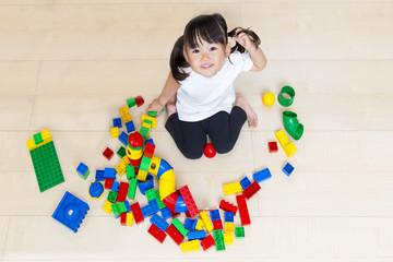 フローリングでブロック遊びをしながら見上げる幼い女の子