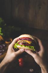 Man eating cheeseburger. Hands holding cheeseburger closeup view selective focus