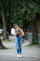 Beautiful young woman enjoying in walk with her little red poodle puppy.