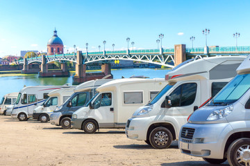 Close up motorhomes parked in a row on background The Saint-Pierre bridge passes over the Garonne river in Toulouse, France