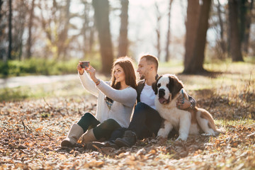 Young couple enjoying in park together with their Saint Bernard puppy and taking selfie photo.