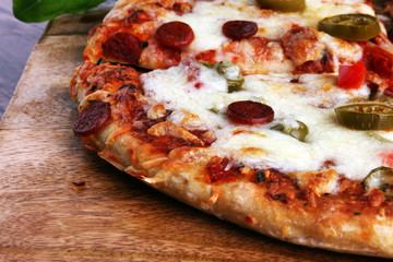 Hot pizza slice with melting cheese on a rustic wooden table. Italien food concept