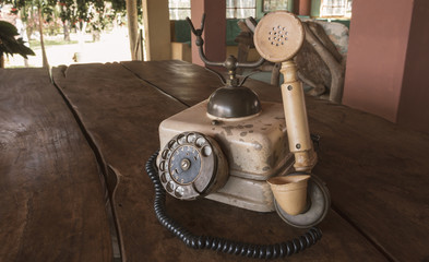 Vintage - Old Beige phone retro on a wood table - 80's concept image