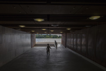 Lonely young boy with umbrella in long tunnel walkway with the white light at the end